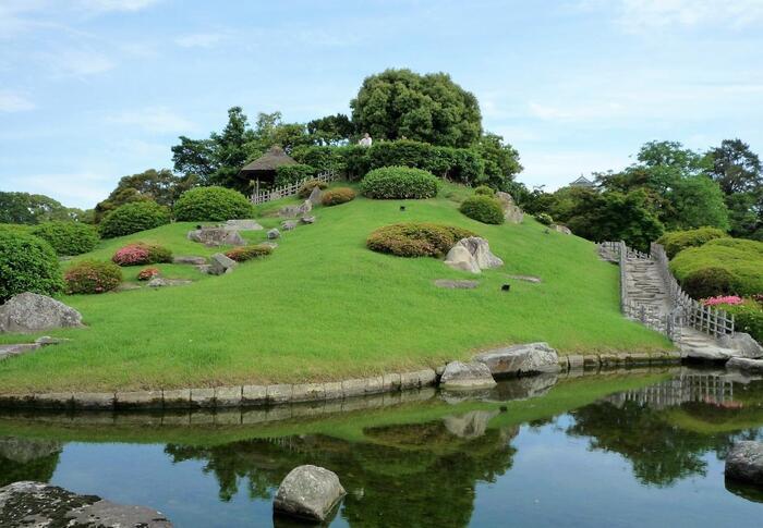 変化に富んだ光景を楽しめる後楽園。こちらの唯心山(ゆいしんざん)は園内を一望できるスポットとして人気があります。斜面にはツツジやサツキが植えられており、花季には紅白の花で美しく彩られます。