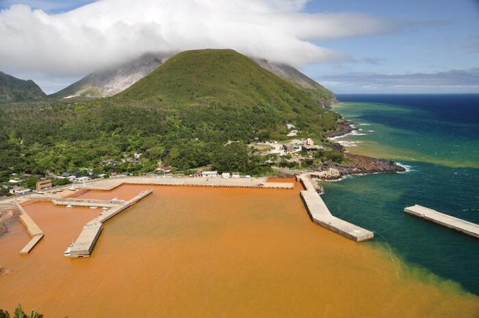 """薩摩諸島の北部にある「硫黄島」は、硫黄岳が活発に噴煙を上げ続ける火山島です。フェリーで入港すると港の色にびっくり。港周辺では鉄分をたっぷり含んだ温泉が湧き出しているため、こんな色に染まるのだそう。""""恋人岬""""の展望台から眺めるとよく見渡せますよ。"""