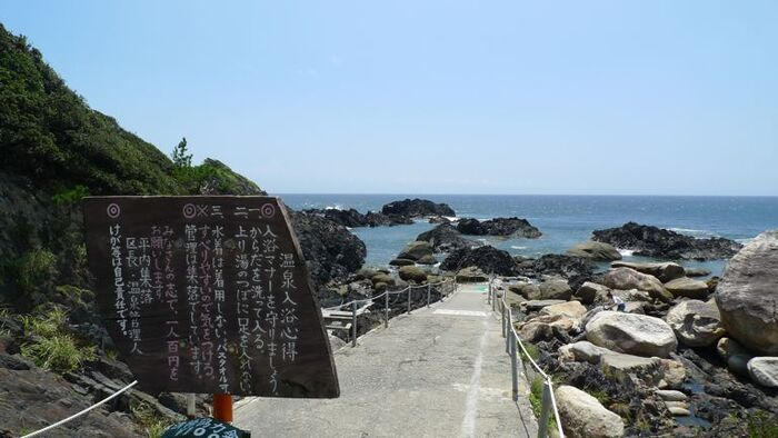 世界遺産の島として有名な屋久島にも、実は知る人ぞ知る温泉スポットがあるんです。「平内海中温泉(ひらうちかいちゅうおんせん)」と呼ばれる露天温泉があるのは、島の南端に位置する場所。海へ下りていく道の入り口には、注意点が書かれた看板や、入湯料200円を支払う箱があります。