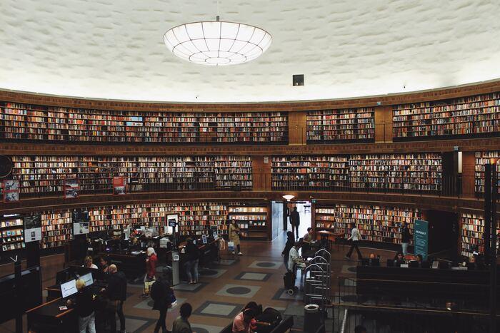 """図書館の正面入り口から、階段を少し登ると、そこには360度一面に、本の壁が広がります。スウェーデンの建築家、エーリック・グンナール・アスプルンド(Erik Gunnar Asplund)は、""""北欧近代建築の親""""としても親しまれており、そんな彼が生み出した「ストックホルム市立図書館」は、世界中に多くのファンを持ち、毎年多くの方々が訪れています。"""