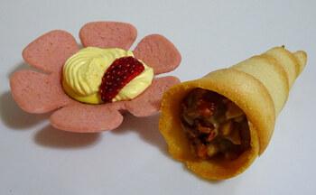 「ストロベリータルティン」は、お花の形をしたかわいいお菓子。花びらをかたどったストロベリータルトに、ラムカスタードクリームやフリーズドライの苺をトッピングしています。  「森のキャラメル」は、チョコレートクリームをサクッとしたラングドシャで包んでいて、カシューナッツ・くるみなどのキャラメルチョコナッツをトッピングしています。