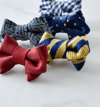 老舗ネクタイメーカーが考案した蝶ネクタイ型の小さなピンブローチ、その名も「tibitie(チビタイ)」。シルクやコットンなど本物のネクタイと同じ生地を使い、一点ずつ丁寧に手作りされています。