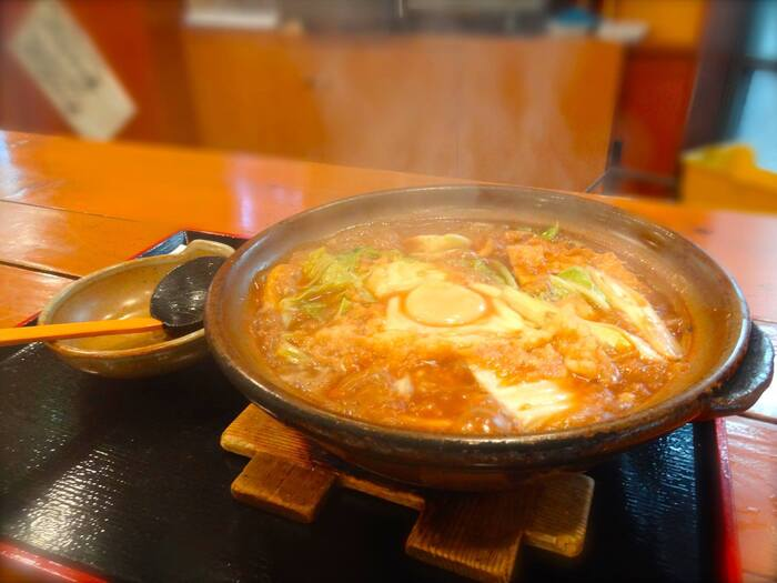白菜・長葱・かまぼこ・鶏肉を煮込み、生卵を落とした『味噌煮込みうどん』。赤みそと白みその2種があります。寒い日にハフハフ頂きたい。