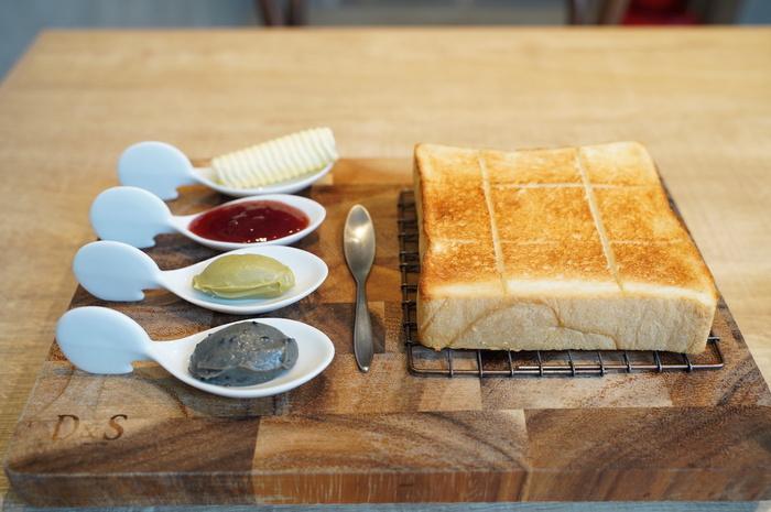 """カフェでは、2種類の食パンがセレクトできます。卵や乳製品不使用の「極美""""ナチュラル""""食パン」は、どんな食べ方とも相性のいい食パンをコンセプトにしていて、麦の優しい風味とほのかな甘さが特徴。  もうひとつの「極生""""ミルクバター""""食パン」は、北海道産の牛乳や生クリーム、国産バターやはちみつの豊かなコクが特徴。どちらか1枚をセレクトしたら、追加料金でジャムやフランス伝統の発酵バターなどをお好みで選びます。"""