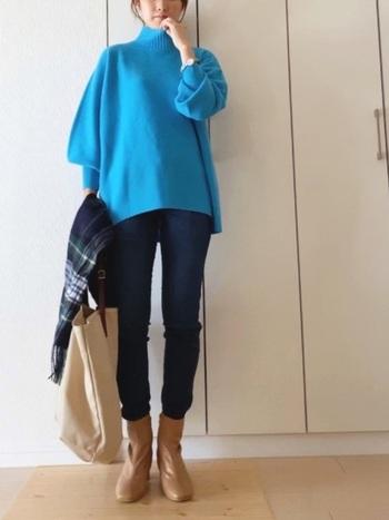 鮮やかなブルーのニット。細身のデニムにベージュのショートブーツを合わせて軽やかに着こなして。