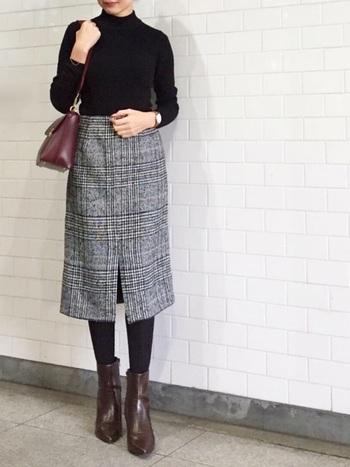 チェックのスカートに黒のタートルニットというベーシックなスタイル。バッグとブーツはブラウン系にして、お洒落度をワンランクアップ。