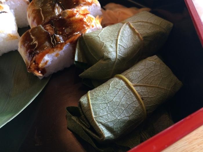 「平宗 吉野本店」の食事どころで提供されている『柿の葉寿司』(画像手前)。お米は地元で穫れるヒノヒカリを使用。 柿の葉寿司の起こりは、海から離れた奈良県吉野地方で、熊野(現・和歌山県)や若狭(現・福井県)で獲れた鯖の保存性を高めるため薄く削いだ身を塩漬けにして酢飯と合わせたものを寿司箱に入れて押した後、抗菌・防腐作用を持つ柿の葉でくるんだもの。明治期に旅館だった同店が宿泊客に出したのが始まりとされています。作家・谷崎潤一郎が随筆「陰影礼賛」の中で柿の葉寿司を絶賛したことで広く知られるようになりました。