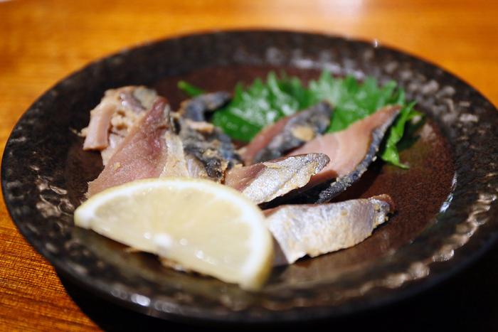 「へしこ」とは、福井県(若狭地方)と京都府北部(丹後半島)の郷土料理。鯖やイワシなどの青魚を塩漬けにした後、さらに糠漬けにしたもの。かつては越冬のための保存食として、現在はご飯のおかずというよりお酒のあてとして珍重されています。 ※画像は「まるさん屋」で提供されているひと皿で、自社の樽に漬け込んで作られたもの。