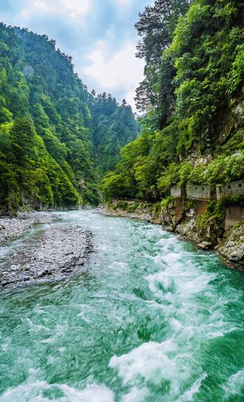富山県の北東部、黒部・宇奈月(うなづき)エリアには、県内有数の観光名所「黒部峡谷(くろべきょうこく)」があります。日本三大渓谷にもなっている、険しいV字谷です。谷の間を流れる黒部川は、エメラルドグリーンの美しい輝き。周囲の山々は、残雪、新緑、万緑、紅葉など、様々な表情を見せてくれます。