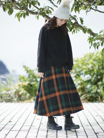 先ほどのトップスと同じ生地をたっぷりと使ったスカートは、まるでブランケットを腰に巻いたような包まれ感。合わせた黒無地のトレーナーは、分厚く編み上げたフリース生地が「やみつきになる心地よさ」と好評なアイテムです。今年は衿がリブ仕様ではなく、トレーナーっぽさが控えめになって登場。