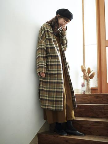 """毛布のような風合いのチェック生地で作られたガウンコートは、冬気分を高めてくれるアイテム。しっかりと厚みがありながら、驚くほど軽く着やすい仕上がりです。合わせたのは""""流氷の天使""""ことクリオネのようなシルエットが独特で可愛らしい、ゆったりとしたサロペット。どちらもベースカラーがブラウン系なので、シンプルだけど秋冬らしい着こなしが叶います。"""
