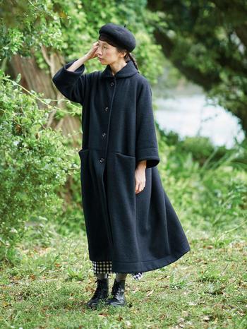 大きな丸衿や広がった短めの袖がレトロモダンな印象のデザインは、昨年秋に登場したコートを黒の縮絨ニット生地でアレンジしたもの。もこっとした素材感と、たっぷりとしたコクーンシルエットが、まさに魔女のイメージにぴったりです。さらに裏地には、ほうきに乗った魔女の姿がジャカードで織り込まれているのだとか……。