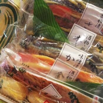 日本酒の醸造過程で発生する酒粕に魚や野菜を漬けた保存食として、平安時代に遡る記録がある〈粕漬け〉。酒粕が魚の臭みをとり除き、アスパラギン酸やグルタミン酸が魚のうま味を引き立ててくれます。  お店秘伝の酒粕に漬けた魚たち。種類は定番の銀鱈や本鰆、鮭のほか、季節に応じて烏賊や銀ひらす、カレイ、帆立貝などが。