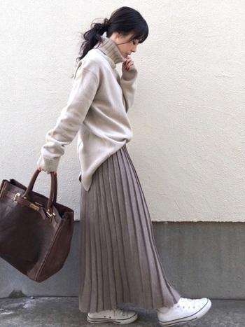 ベージュのタートルネックニットに、同系色のロングプリーツスカートを合わせたコーディネート。ゆるシルエットのニットトップスはフロントだけをタックインして、全体のパランス感を調整しているのがポイント。足元は白のスニーカーで、あえてカジュアルダウンしたスタイリングです。