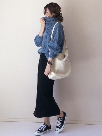 ブルーのタートルネックニットに、黒のタイトスカートを合わせたコーディネートです。白の大きめショルダーバッグが、青×黒のダークトーンに程よい明るさをプラスしています。足元は黒スニーカーで、カジュアルな印象に。