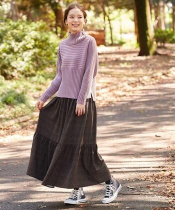 ダークパープルカラーのハイネックニットに、細かなドット柄のスカートを合わせたコーディネートです。フェミニンな雰囲気のアイテム同士の組み合わせですが、あえてハイカットのスニーカーをチョイスすることでスカートスタイルを上手にカジュアルダウンしています。