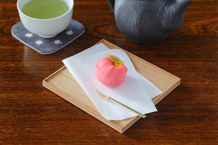 折敷はうつわを使わず、そのまま食べ物をのせても大丈夫です。小さめの折敷にひとつだけお菓子を丁寧に盛り付けると、お皿と同じように使えますね。お懐紙をアレンジするとさらに丁寧な印象に。