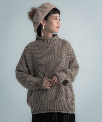 着こなしを間違えると地味に見えかねない色味のニットには、帽子を浅めに被り、印象的な耳飾りをプラス。女性らしさが加わると共に、目線が上に行くので素敵なメリハリが生まれます。