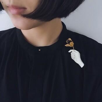 ものがたりを纏う、をテーマに陶でブローチを作る「warabino tomoko」さん。個性溢れる作品デザインは、シンプルな装いを特別なものにしてくれます。  画像はお花を持つ手のブローチ。自分の好きな花を挿して使うという、使い手も参加しながら完成する仕掛けがとてもユニークですね。