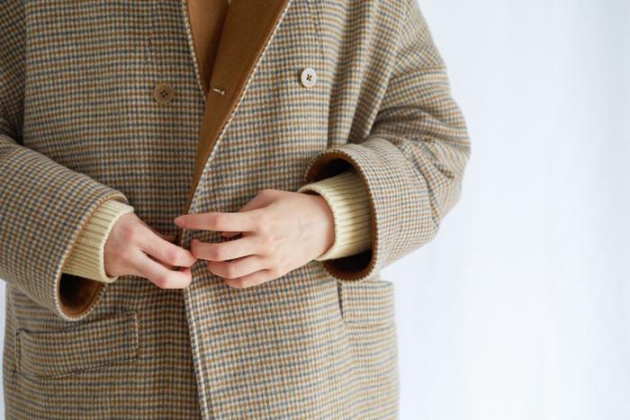 落ち着いた配色のチェック柄コートは、『グランマ ママ ドーター』らしいラウンドカラーに、たっぷりとしたコクーンシルエットがトラッドな雰囲気を醸し出すアイテム。見返し部分には無地の同系色が配されているので、袖を折り返して着ても綺麗にまとまります。