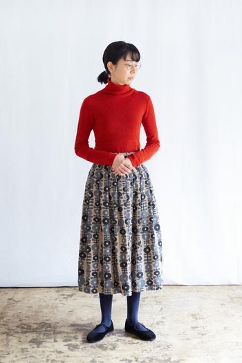 長く着こなせるカラーのひとつである朱赤を差し色に、オリジナルプリントのタックプリーツスカートを合わせた、遊び心あるコーディネート。暗い色が多くなるこの時季、顔周りを明るく華やかに、スカートのふんわりとしたシルエットで、より女性らしさを表現してくれます。