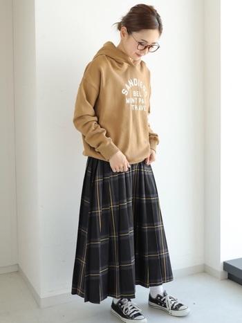 ロゴ入りパーカーと大きめチェックのプリーツスカートで、可愛らしい大人カジュアルな着こなし。シンプルながら、メガネも重要なおしゃれアイテムのポイントです。