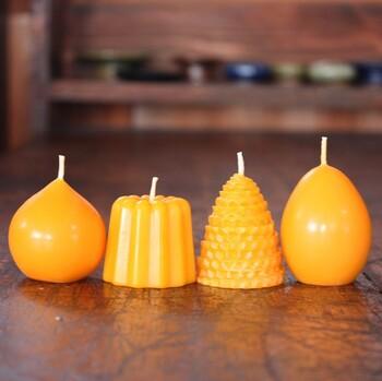 カヌレやたまごなど、4つの形のキャンドルセット。鮮やかなオレンジ色は、天然の蜜蝋由来の色なんです。プレゼントにもぴったりです。