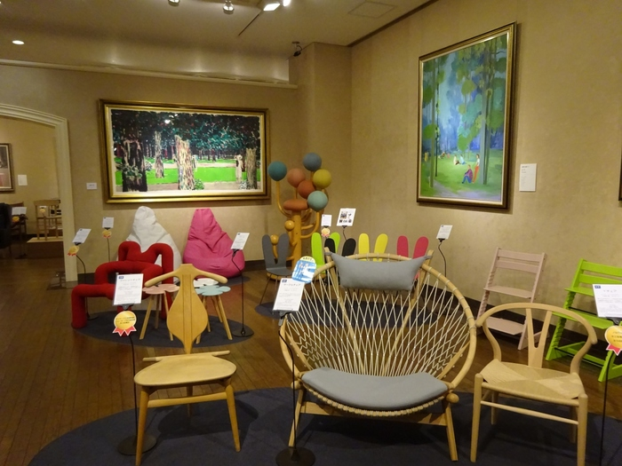 コンセプトごとに7部屋の展示室があり、前半は「世界の名作家具デザイン展」、後半は「東西名画展」と分かれています。その展示方法が一風変わっており、造形が美しいデザインチェアや、ポップな色がかわいい家具など、絵画の世界と家具とがうまく溶け込むよう、同じ空間に展示されているのが特徴です。