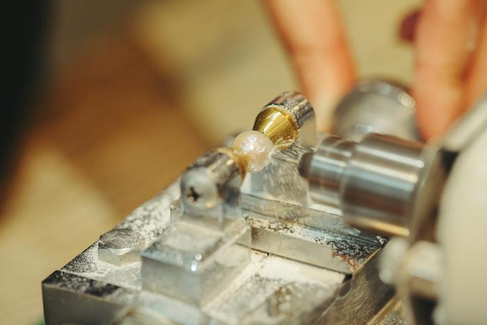 専用のマシンにセットして穴を開けていくと、ギューンという機械的な音が響いた。びわ湖真珠は硬いため、割れることはほとんどないという。ただし、上手に穴を開けないと針が摩耗してしまうため、テクニックが必要。難しい形のものは杉山さんが担当することが多いという