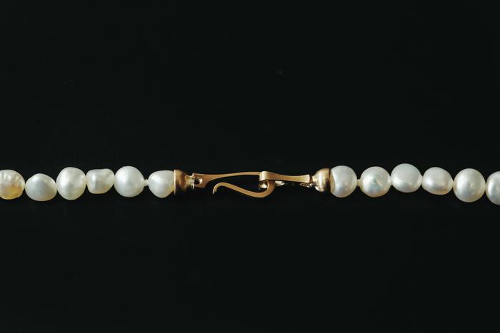 ブレスレットが回ってきてしまったときに鎖が見えてしまうと少し格好悪い。そんな問題を解決するために、どの面がきてもスタイリッシュに見えるよう、リング状の留め具(デザインは「PROOF OF GUILD」)を使用。真珠の美しさはもちろんのこと、細部にまで女性にうれしい気配りが施されている