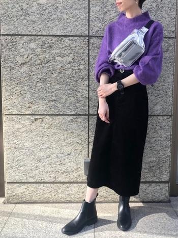 鮮やかなパープルのニットに合わせたのは、ブラックのタイトスカート。メタリックなボディバックやスポーティな時計を合わせたスタイリッシュな着こなしが素敵です。