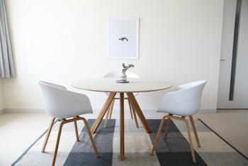 斜めに脚が入ったラウンドテーブルは、三人掛けにぴったり。  こちらはニュアンスのあるオフホワイトの、「HAY(ヘイ)」のテーブル。AACのチェアがよく似合っていますね。どこから見ても美しいラインに心がときめきます。