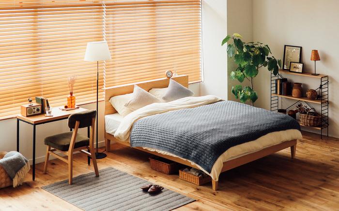 木のぬくもり溢れる素敵なベッドルーム。ベッドとデスクの間に背の高いフロアライトを配置することで、ワンルームでもメリハリのあるおしゃれな空間に。