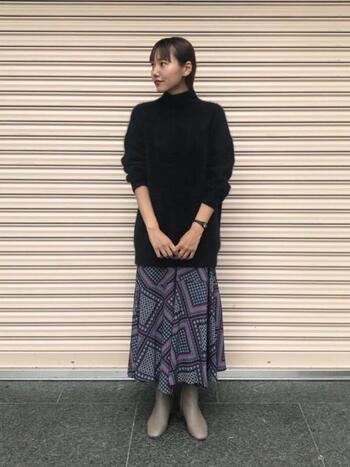 ネイビーのロングニットとテキスタイルが可愛いロングスカートのダークトーンコーデ。ブラックやホワイトではなく、モカのショートブーツを合わせることで抜け感が生まれます。