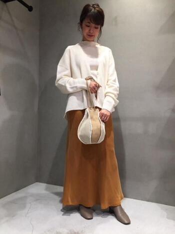 白ニットに明るいカラーのスカート、そしてコーデのポイントに丸いバッグを合わせて遊びを取り入れて。コーデの雰囲気を壊さないよう、足元はスカートと一体感の出る優しいブラウンのショートブーツに。