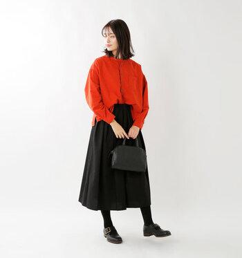 赤のスタンドカラーシャツを、黒のロングスカートに合わせた着こなし。シャツ以外は黒系のダークトーンでまとめて、赤を主役にしたツートーンコーデに仕上げています。アウターも黒で揃えて、赤シャツをちらりと覗かせても素敵♪