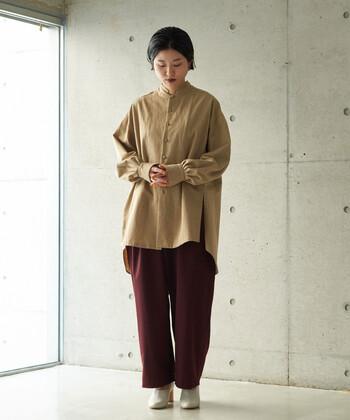 ベージュのドレスシャツに、赤系のワイドパンツを合わせたコーディネート。無地アイテム同士の組み合わせながら、スタイリッシュなカラーリングでおしゃれ見えを叶える着こなしです。