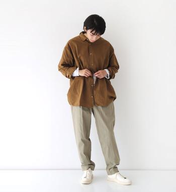 ブラウンのシャツにベージュのパンツを合わせて、落ち着いたカラーリングでまとめたナチュラルなコーディネートです。足元は白のシューズで爽やかな印象に。袖からちらりと覗かせた、白の長袖インナーが程よいアクセントをプラスしてくれます。