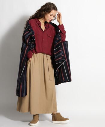 ボルドーのカラーシャツに、ベージュのスカートを合わせたレディライクなコーディネートです。マルチストライプ柄のストールをプラスして、シンプルコーデにワンアクセントを加えています。スカートと色味を合わせたシューズが、全体に統一感をプラス♪