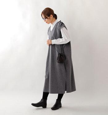 グレーのジャンパースカートに、白のフリルブラウスを合わせたコーディネートです。ショートブーツやタイツとバッグを黒で揃えて、大人のモノトーンコーデにまとめています。