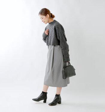 グレーのチェック柄ジャンパースカートの上から、同系色のショート丈ニットをプラスしたコーディネート。ハイウエストのスカートを穿いているようなスタイリングになり、ジャンスカのいつもとは違う着こなしが楽しめます。小物は黒で揃えて、上品なベーシックコーデに。