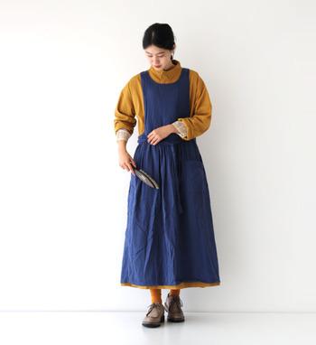 ネイビーのジャンパースカートに、マスタードからのシャツを合わせた季節感たっぷりなスタイリング。薄いブラウンのシューズから覗くレッグアイテムも、シャツとカラーを合わせて統一感のあるコーディネートに仕上げています。
