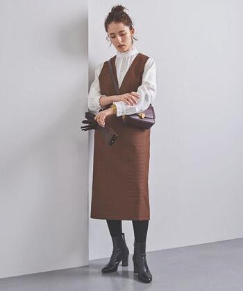 ブラウンカラーのチェック柄ジャンパースカートに、フリルネックのブラウスを合わせたコーディネートです。ヒールのショートブーツとタイツでクールにまとめて、ブラウンのショルダーバッグと手袋でちょっぴりレトロな着こなしに♪