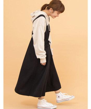 黒のジャンパースカートに、ゆったりシルエットのパーカーを重ねた着こなし。足元はパーカーと色を揃えたスニーカーで、とことんカジュアルにスタイリングしています。靴下で素足をチラ見せしていますが、寒くなる季節にはカラータイツでワンアクセントをプラスしても◎。