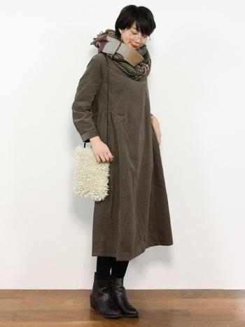 こげ茶色のシンプルなワンピース。チェックのマフラー&革のブーツで、トラッドな印象に。