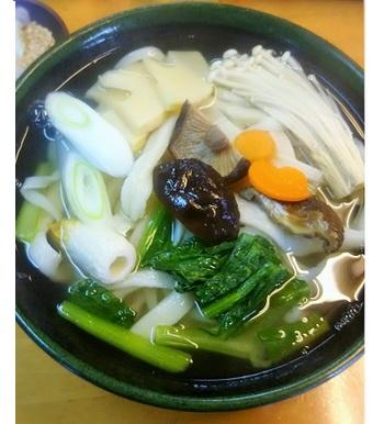 小松菜に長ねぎ、にんじんなどたっぷりな野菜に、椎茸、エノキタケ、筍、竹輪を加えた「野菜うどん」。(筆者撮影)