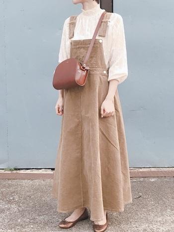 カジュアルなデザインのジャンパースカート。透け感あるスタンドカラーのブラウスとかっちり目の革バッグで、あえてフェミニンに着こなして。