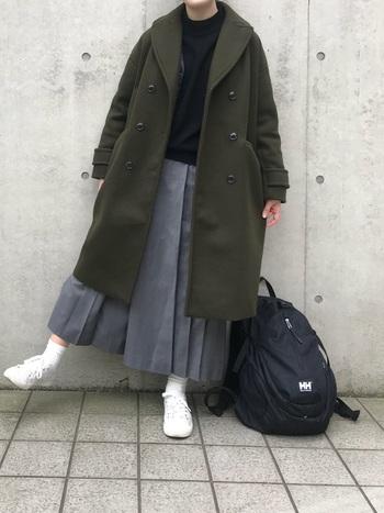 オリーブカラーが素敵なコートとグレーのロングスカートを合わせたスクール風の着こなし。リュックをプラスしてアクティブに。