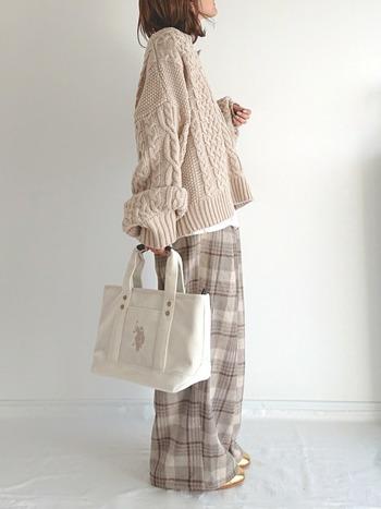 ベージュのざっくりニットに同系色のチェックパンツを合わせた全体的に統一感のある女性らしい装い。クリームカラーともったりした袖やサイズ感など、ゆるく柔らかな甘さを感じさせてくれるコーディネートは、冬のデートにも最適ですね。