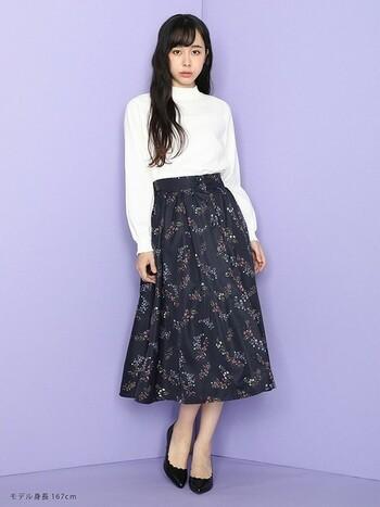 白のハイネックブラウスは花柄スカートと合わせれば甘い雰囲気に。花柄スカートは、明るい色を選ぶとガーリーな印象になり過ぎるので、シックなカラーを選ぶと上品な佇まいになりますよ。